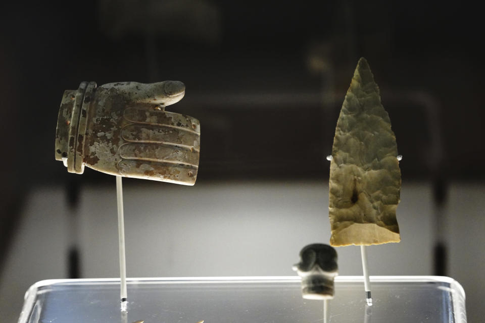 """A hand carved stone and arrowhead are shown as part of the exhibition """"The Greatness of Mexico"""" displaying for the first time in the country more than 800 pieces repatriated from abroad in the last three years and others that were in safekeeping and confiscation warehouses, at the Anthropology Museum in Mexico City, Friday, Oct. 1, 2021. (AP Photo/Marco Ugarte)"""