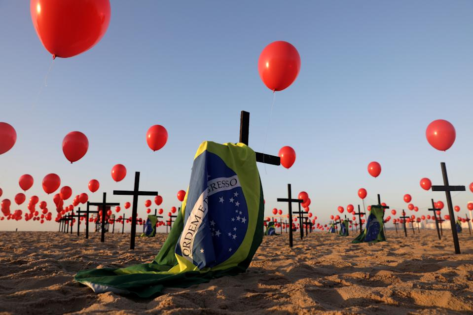 Crosses, balloons and Brazilian flags are seen at Copacabana beach, placed by members of the NGO Rio de Paz in tribute to the 100,000 victims of the coronavirus disease (COVID-19) in the country, in Rio de Janeiro, Brazil August 8, 2020. REUTERS/Ricardo Moraes     TPX IMAGES OF THE DAY