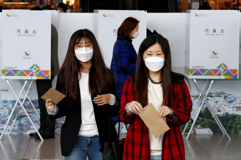 Voters cast absentee ballots for the parliamentary election at a polling station in Seoul