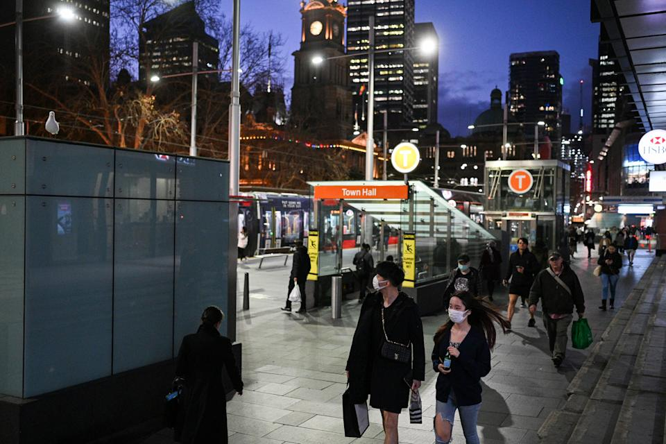 People in face masks walk around the entrances of the Town Hall train station in Sydney CBD during the coronavirus pandemic.