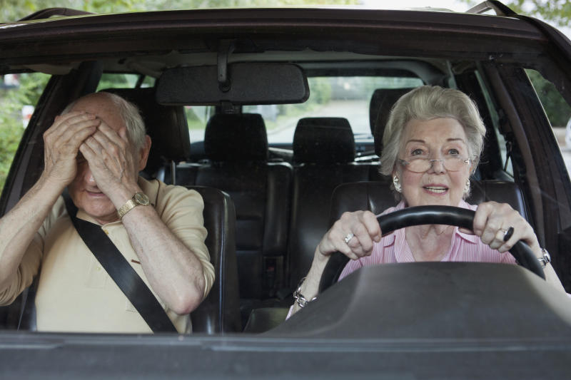 Woman has trouble driving while man in passenger seat despairs