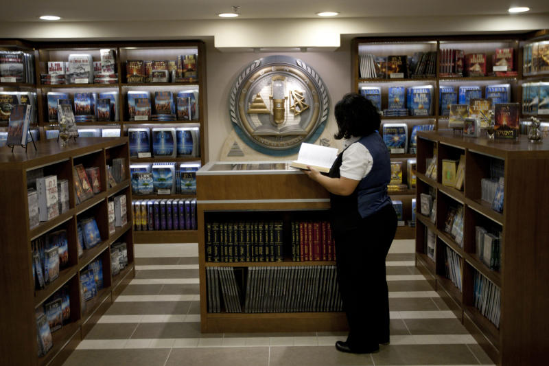 In this Wednesday, Nov. 7, 2012, photo a librarian goes through books at the library of the Scientology center in the port city of Jaffa Tel Aviv, Israel. Near the ancient market of Israel's biblical port city of Jaffa, a striking new white building has been erected amid the mustard tableau of surrounding stores and homes. The elegant 60,000 square-foot center sticks out for another reason: It is the new headquarters of Scientology in the Holy Land. (AP Photo/Ariel Schalit)