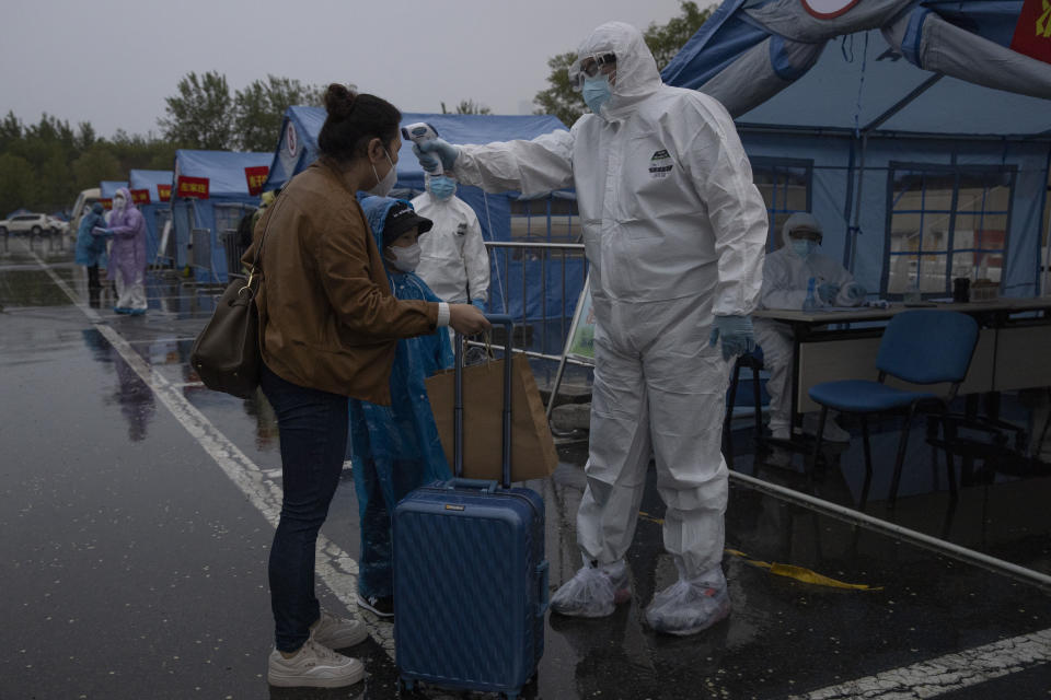 A worker in protective overalls take the temperature of a traveler from Wuhan before directing her to her district in Beijing on Sunday, April 19, 2020. Wuhan, the city at the center of the global coronavirus epidemic, lifted a 76-day lockdown early April and allowed people to leave for destinations across China. (AP Photo/Ng Han Guan)