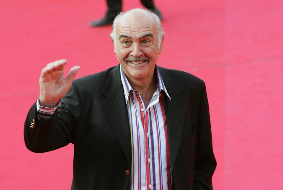 Sir Sean Connery waves to cameras while on a red carpet.