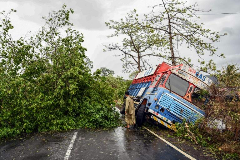A truck and uprooted trees are seen on a road in the coastal town of Alibag following Nisarga's landfall in India
