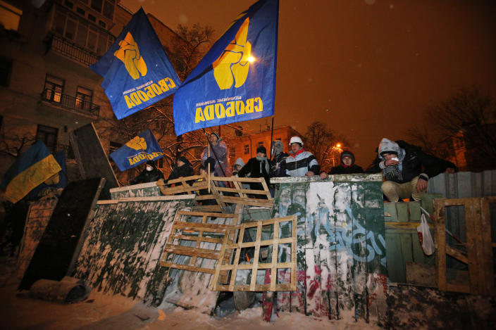 Pro-European Union activists stand on their barricades as riot police prepare to storm at the Ukrainian presidential administration building in Kiev, Ukraine, Tuesday, Dec. 10, 2013. Heavily armed riot troops broke into the offices of a top Ukrainian opposition party in Kiev and seized its servers Monday, the party said, as anti-government protests crippled the capital for yet another day. Elsewhere police dismantled or blocked off several small protest tent camps set up near key national government buildings in the city. (AP Photo/Alexander Zemlianichenko)