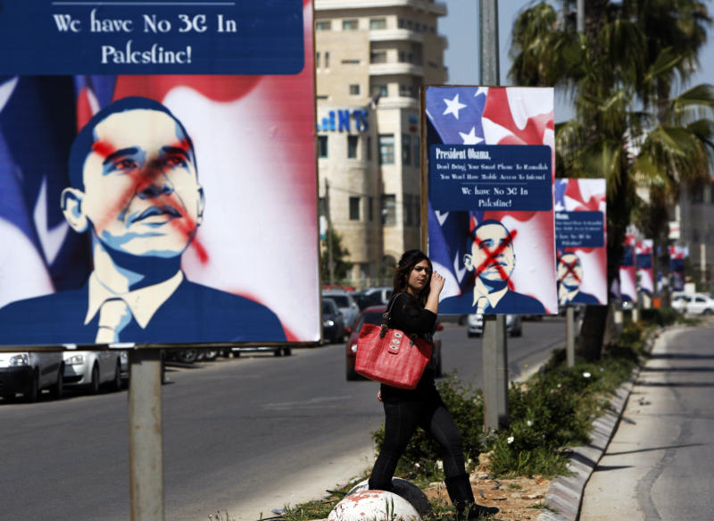 FILE-- In this Friday, March. 15, 2013 file photo, a Palestinian woman walks past vandalized posters showing US President Barack Obama, in the West Bank city of  Ramallah. When he visits the region next week President Obama will find a disillusioned Palestinian public, skeptical about his commitment to promoting Mideast peace, and who accuse him of unfairly favoring Israel. (AP Photo/Majdi Mohammed, File)