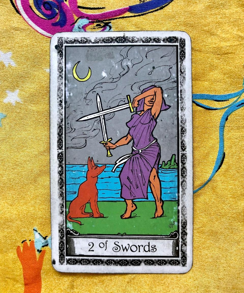 """<strong>Two of Swords</strong><br><br>Potter's first pull: a Two of Swords, which she said is kind of like a stalemate. """"We have to make a decision,"""" she said. """"The Two of Swords is like, don't hold back — say what you're thinking and let someone know.""""<br><br>Right off the bat, the cards want you to be open about your love this <a href=""""https://www.refinery29.com/en-us/2018/02/189362/unique-valentines-gifts"""" rel=""""nofollow noopener"""" target=""""_blank"""" data-ylk=""""slk:Valentine's Day"""" class=""""link rapid-noclick-resp"""">Valentine's Day</a>. Tell your crush you dig them, let your partner know how much you appreciate them, or tell your best friend that you're grateful for their support during the past year. <br><br>The Two of Cards is actually showing that you have an option here: Be open with your affections, or don't. But if you choose the latter, know that the moment can pass you by. """"I feel like we can get caught up in the, 'What if they don't like me?' or 'What if they don't respond in the way I want them to?,'"""" Potter said. """"But if you don't try, you'll never know, and to me if we've learned anything from what we're facing as a planet it's that nothing's guaranteed and we shouldn't really put things off.""""<span class=""""copyright"""">Photo: courtesy of Sarah Potter.</span>"""