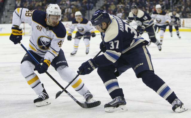 Buffalo Sabres' Matt Hunwick, left, and Columbus Blue Jackets' Markus Hannikainen, of Finland, chase the puck during the second period of an NHL hockey game Tuesday, Jan. 29, 2019, in Columbus, Ohio. (AP Photo/Jay LaPrete)