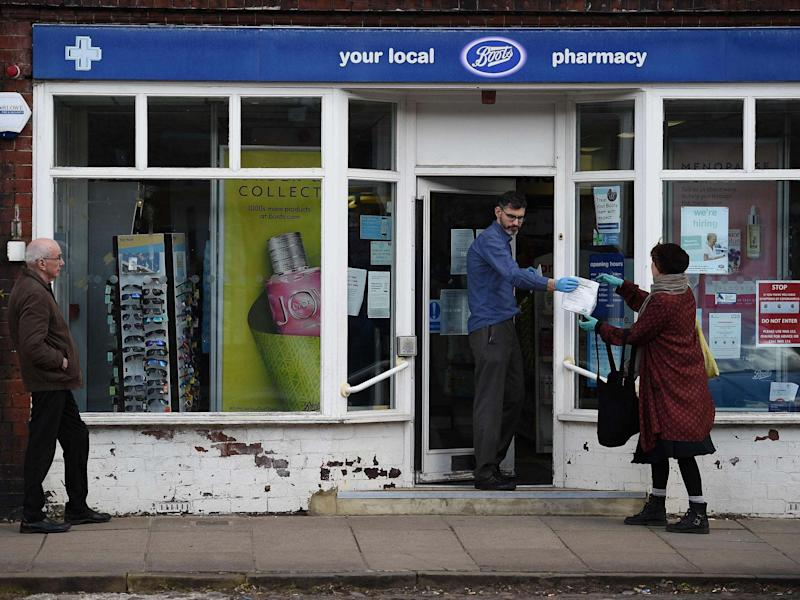 An employee hands a customer her prescription medicines as she adheres to social distancing guidelines outside a Boots pharmacy store in York: AFP via Getty Images