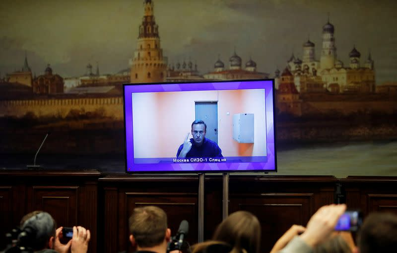 FILE PHOTO: Russian opposition leader Alexei Navalny is seen on a screen via a video link during a court hearing to consider an appeal on his arrest, outside Moscow