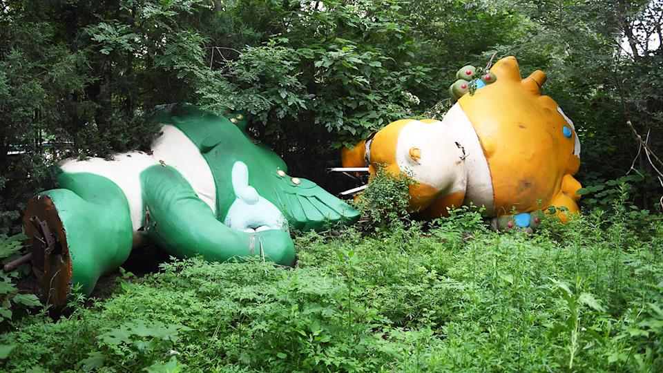 Two of the five mascots for the Beijing Olympics lying among trees behind an abandoned, never-completed mall.