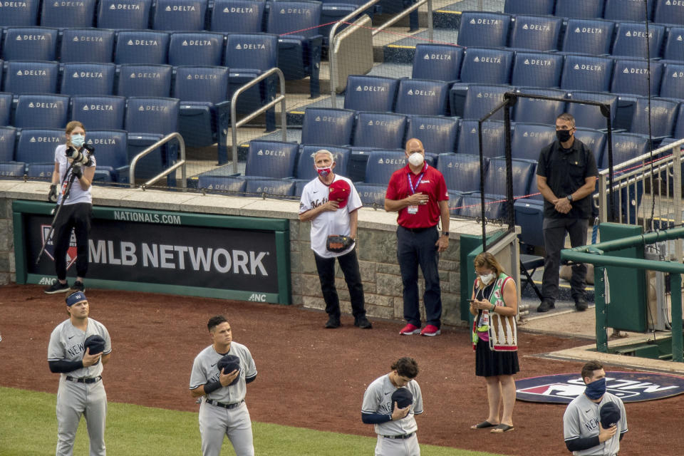 Director of the National Institute of Allergy and Infectious Diseases Dr. Anthony Fauci, center, holds his hat during the playing of the National Anthem before throwing out the ceremonial first pitch at Nationals Park at an opening day baseball game between the New York Yankees and the Washington Nationals, Thursday, July 23, 2020, in Washington. (AP Photo/Andrew Harnik)