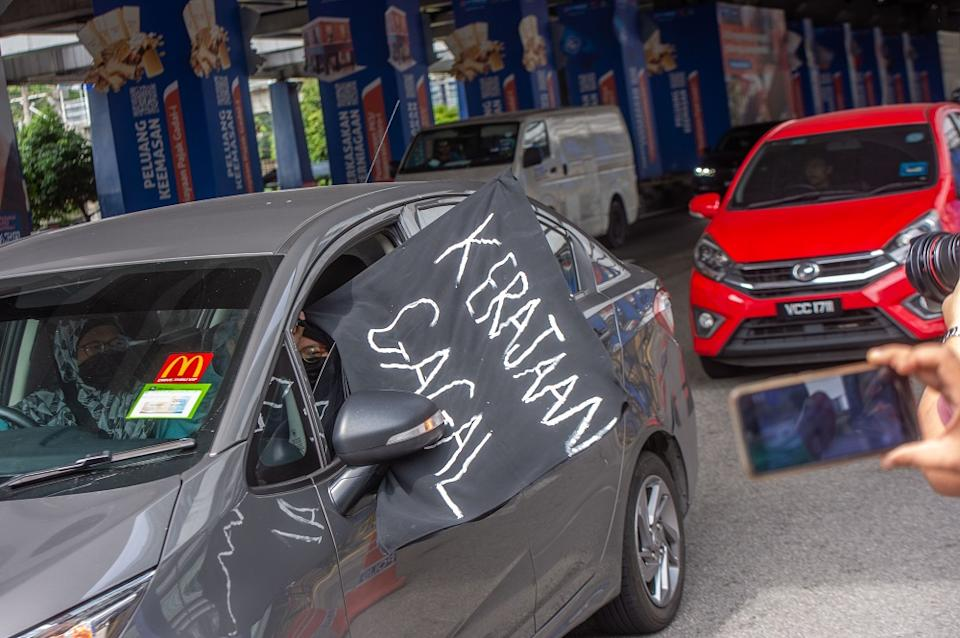 A convoy of cars with black flags are seen around the Kuala Lumpur city centre during a protest July 24, 2021. — Picture by Shafwan Zaidon