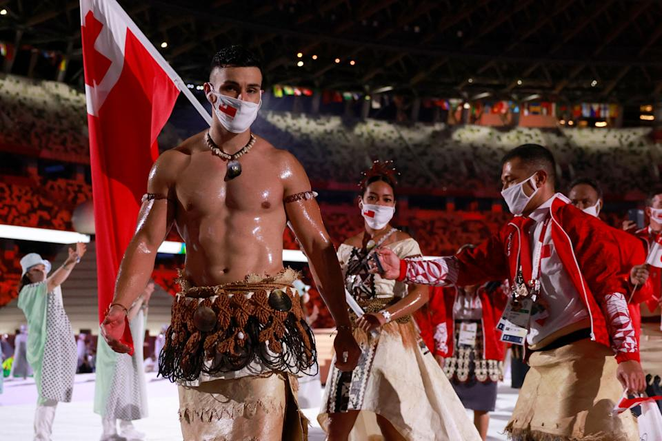 Tonga's flag bearers Pita Taufatofua (L) and Malia Paseka  (2L)  lead their delegation as they parade  during the opening ceremony of the Tokyo 2020 Olympic Games, at the Olympic Stadium, in Tokyo, on July 23, 2021. (Photo by Odd ANDERSEN / AFP) (Photo by ODD ANDERSEN/AFP via Getty Images)
