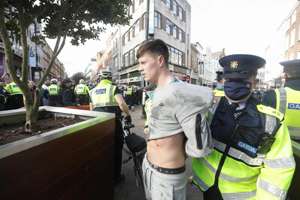 Gardai restrain a protester dring an anti-lockdown protest in Dublin city centre.