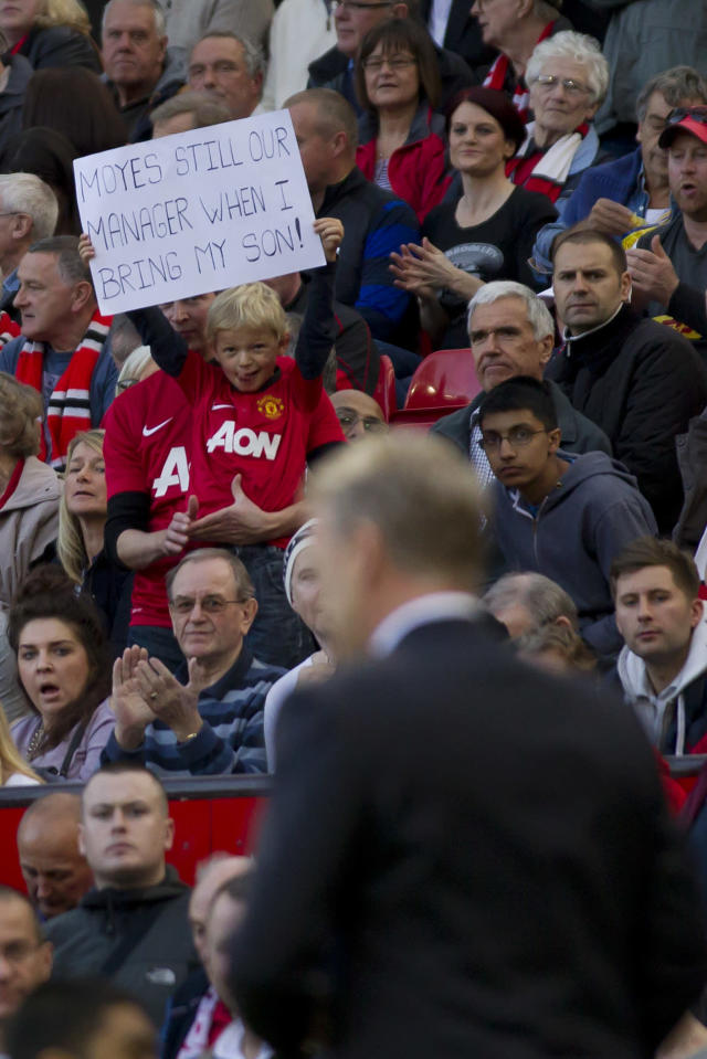 A young supporter holds up a sign as Manchester United's manager David Moyes, below, makes his way down the touchline during his team's 1-1 draw against Southampton in their English Premier League soccer match at Old Trafford Stadium, Manchester, England, Saturday Oct. 19, 2013. (AP Photo/Jon Super)