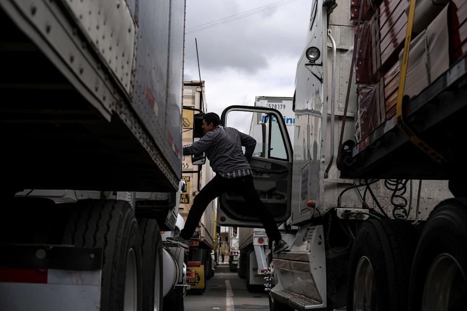 TOPSHOT - A cargo truck driver talks to a fellow driver, while lining up to cross to the United States near the US-Mexico border at Otay Mesa crossing port in Tijuana, Baja California state, Mexico, on April 4, 2019. - US President Donald Trump is expected to visit a section of the border fence in Calexico during his tour to California on Friday. (Photo by Guillermo Arias / AFP)        (Photo credit should read GUILLERMO ARIAS/AFP via Getty Images)