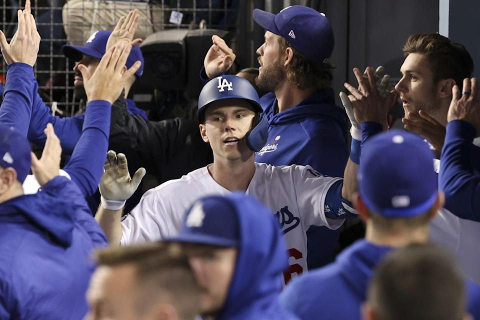 Will Smith celebrates with teammates in the dugout after hitting a two-run home run for the Dodgers in the eighth inning.