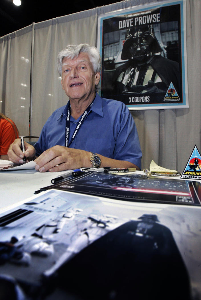 FILE - In this file photo dated Saturday, May 26, 2007, actor David Prowse, who was the man in the black Darth Vader suit in the first Star Wars film, signs autographs at Star Wars Celebration IV, marking the 30th anniversary of the release of the first film in the Star Wars saga, in Los Angeles, USA. The British actor, Prowse who played Darth Vader in the original Star Wars trilogy, has died aged 85 on Saturday, according to an announcement by his agent Sunday Nov. 29, 2020. (AP Photo/Reed Saxon, FILE)