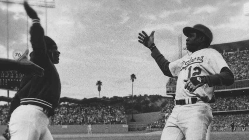 Glenn Burke, left, goes to give a high-five to teammate Dusty Baker after Baker hit a home run in 1977.