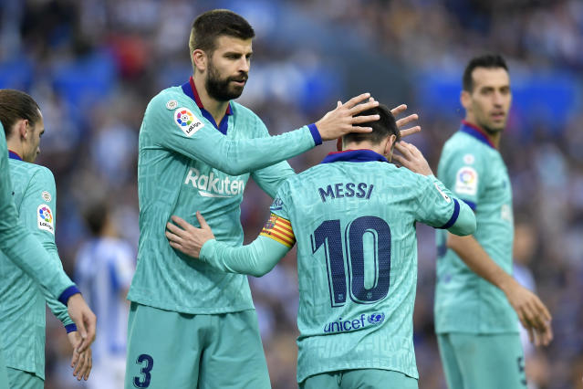 Barcelona's Gerard Pique, center left, congratulates Lionel Messi after he served teammate Luis Suarez to score their side's second goal during the Spanish La Liga soccer match between Real Sociedad and Barcelona, at Anoeta stadium, in San Sebastian, Spain, Saturday, Dec. 14, 2019. (AP Photo/Alvaro Barrientos)