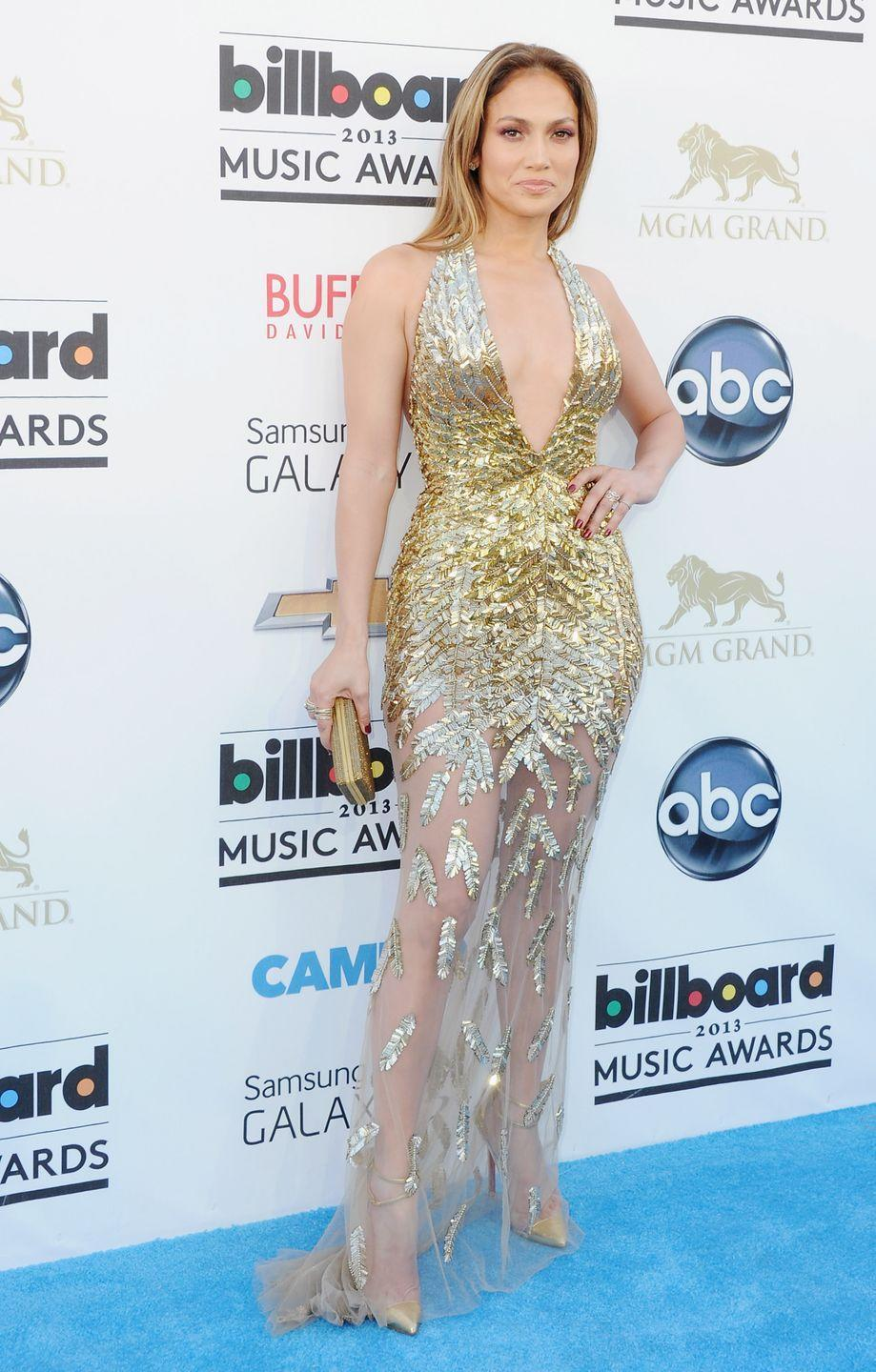 <p>The pop star shines in a plunging gold embellished dress with matching strappy heels and clutch at the Billboard Music Awards.</p>