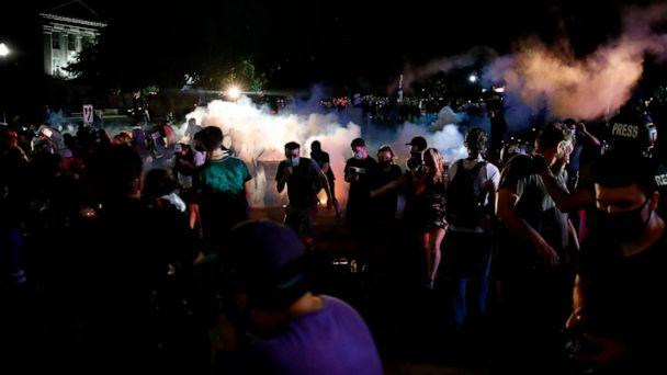 PHOTO: Protestors run for cover as police shoots teargas in an effort to disperse the crowd outside the County Courthouse during demonstrations against the shooting of Jacob Blake in Kenosha, Wis. on Aug. 25, 2020. (Kamil Krzaczynski/AFP via Getty Images)