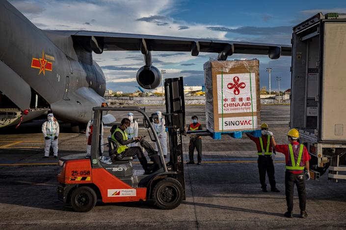 """A crate containing Sinovac Biotech COVID-19 vaccines is loaded into a truck upon arriving at Ninoy Aquino International Airport on Feb. 28, 2021 in Manila. Sunday's delivery marks the first time the Philippines received official coronavirus vaccines, the last country in ASEAN to do so<span class=""""copyright"""">Ezra Acayan—Getty Images</span>"""