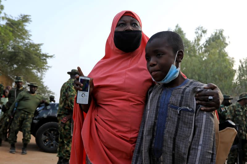 A woman looks on as he receives her son, who had been rescued by the Nigerian security forces in Katsina