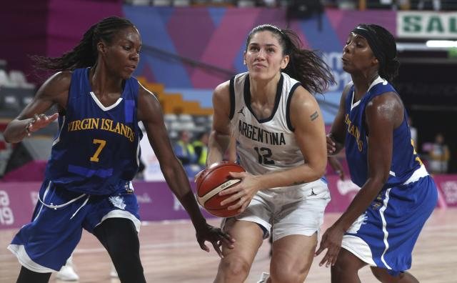 Ornella Santana of Argentina, center, drives through Natalie Day, left, and Sedeja Fieulleteau, of the Virgin Islands during the women's basketball match at the Pan American Games in Lima, Peru, Thursday, Aug. 8, 2019. (AP Photo/Martin Mejia)