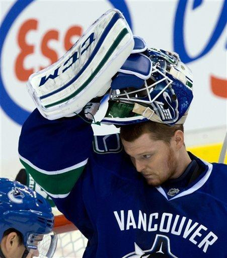 Vancouver Canucks' goalie Cory Schneider lifts up his mask after allowing a fifth goal to the Anaheim Ducks before being replaced by Roberto Luongo during second period NHL hockey action in Vancouver on Saturday, Jan. 19, 2013. (AP Photo/The Canadian Press, Darryl Dyck