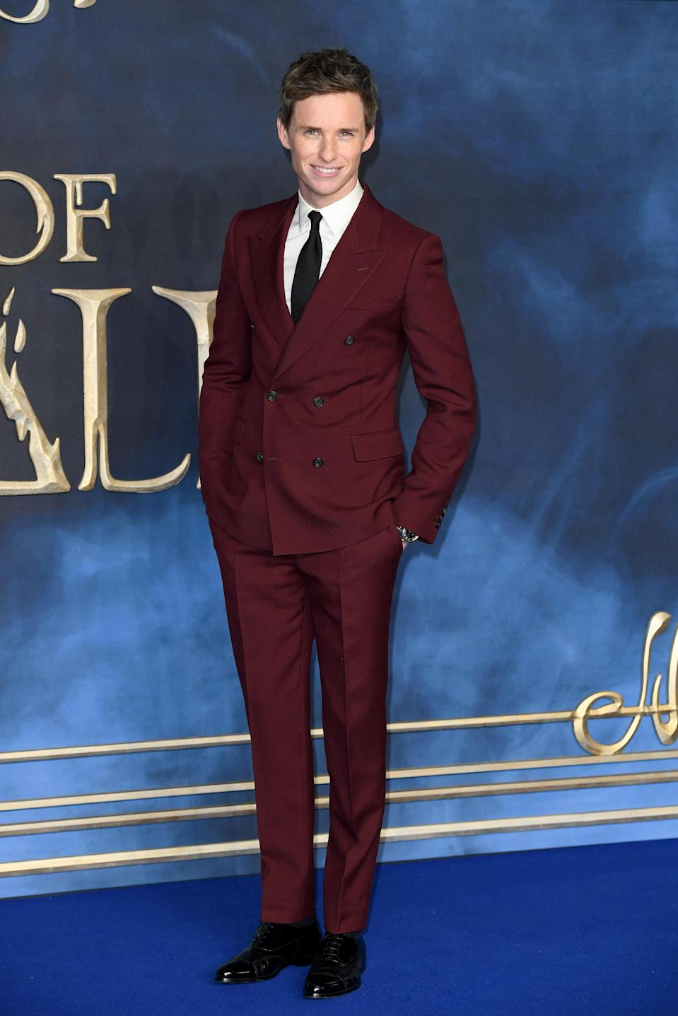 <p>Eddie Redmayne wore a burgundy Alexander McQueen suit at the UK premiere of 'Fantastic Beasts: The Crimes Of Grindelwald' at the Cineworld Leicester Square, London, UK. <em>[Photo: Getty]</em> </p>