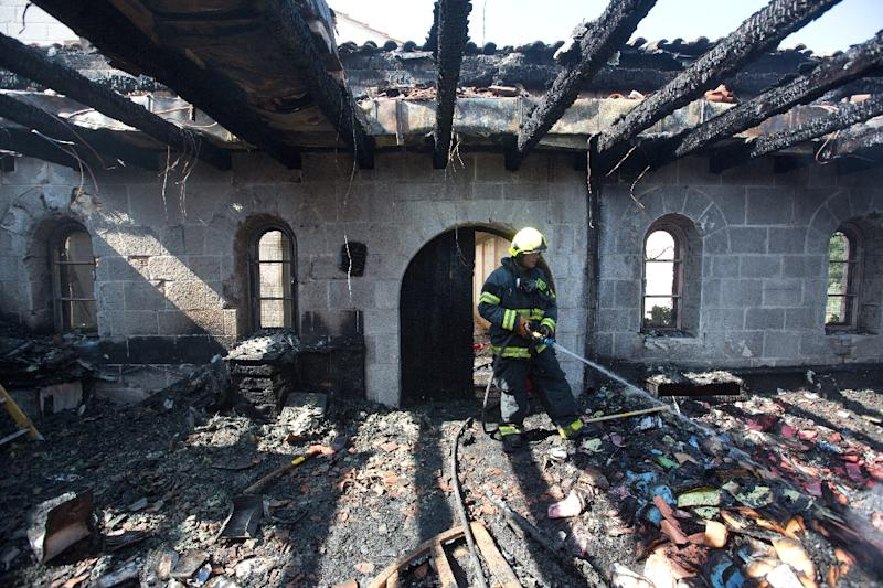 A fireman sprays water on debris at the Church of the Multiplication in Tabgha, northern Israel, on June 18, 2015 after a suspected arson attack