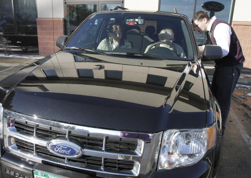 FILE - In this Dec. 30, 2010 file photo, George and Sheila Snyder, of Washington, Vt., take delivery of their new 2011 Ford Escape from salesman John Cassel, right, at the Formula Ford dealership showroom in Montpelier, Vt. Shoppers pushed retail sales up for a seventh straight month although the increase was the weakest showing since June.(AP Photo/Toby Talbot, file)