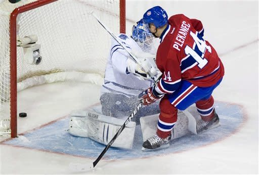 Montreal Canadiens' Tomas Plekanec (14) scores against Toronto Maple Leafs goaltender Ben Scrivens during the first period of an NHL hockey game in Montreal, Saturday, April 7, 2012. (AP Photo/The Canadian Press, Graham Hughes)