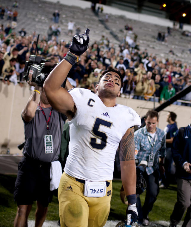 """In this Sept. 15, 2012 photo, Notre Dame linebacker Manti Te'o points to the sky as he leaves the field after a 20-3 win against Michigan State in East Lansing, Mich. In a shocking announcement, Notre Dame said Te'o was duped into an online relationship with a woman whose """"death"""" from leukemia was faked by perpetrators of an elaborate hoax. (AP Photo/South Bend Tribune, James Brosher) MANDATORY CREDIT"""