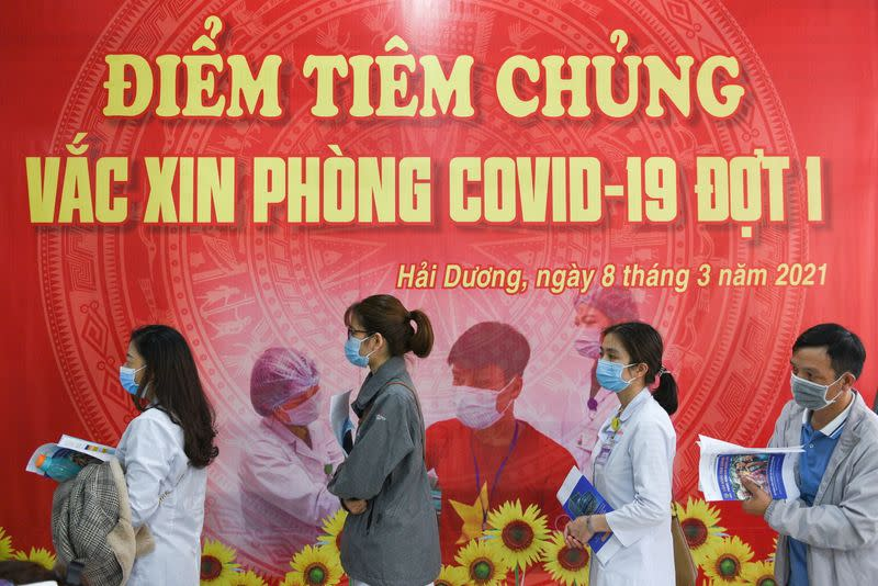 Health workers wait for their turn as Vietnam starts its official rollout of AstraZeneca's COVID-19 vaccine, in Hai Duong
