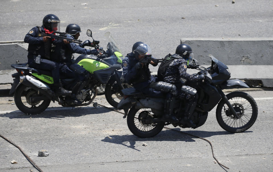 FILE - In this April 30, 2019 file photo, police aim weapons at opponents to Venezuela's President Nicolas Maduro during clashes in Caracas, Venezuela, hours after opposition leader Juan Guaidó took to the streets in a bold and risky attempt to lead a military uprising against the president. Last April, as a military uprising roiled Venezuela, Maduro's socialist government ordered pay TV providers to immediately cease transmission of CNN and the BBC. DirecTV, which is wholly owned by AT&T, quickly obliged, yanking the two networks off the air. (AP Photo/Fernando Llano, File)