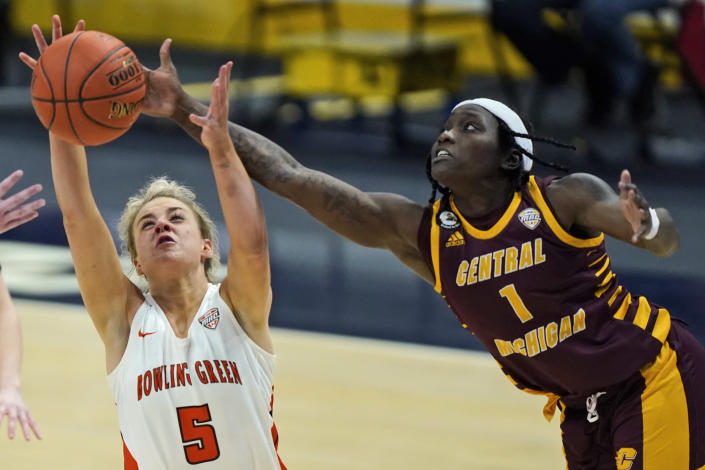Bowling Green's Elissa Brett (5) and Central Michigan's Micaela Kelly (1) battle for a loose ball during the second half of an NCAA college basketball game in the championship of the Mid-American Conference tournament, Saturday, March 13, 2021, in Cleveland. Central Michigan won 77-72. (AP Photo/Tony Dejak)