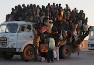 <p>Foreign workers from Nigeria, Ghana, and other African countries pile in the back of a truck with their belongings trying to leave the besieged city of Misrata April 18, 2011 as the sun sets on the port in Misrata, Libya. Thousands of foreign workers and Libyans alike are trying to leave war-torn Misrata, as fighting continued between Libyan government forces and anti-government rebels. The Libyan government has come under international criticism for using heavy weapons and artillery in its assault on Misrata, which can cause civilian casualties. (Photo by Chris Hondros/Getty Images) </p>