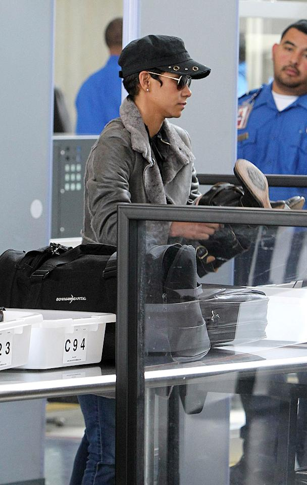 Halle Berry removed her boots, but not her coat, hat, or sunglasses when  she tried to get through LAX last March. Surely, that glaring TSA agent  set her straight.