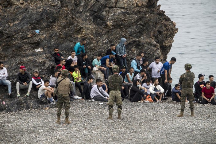 Moroccan men and boys sit as Spanish Army cordon off the area at the border of Morocco and Spain, at the Spanish enclave of Ceuta, on Tuesday, May 18, 2021. Ceuta, a Spanish city of 85,000 in northern Africa, faces a humanitarian crisis after thousands of Moroccans took advantage of relaxed border control in their country to swim or paddle in inflatable boats into European soil. Around 6,000 people had crossed by Tuesday morning since the first arrivals began in the early hours of Monday, including 1,500 who are presumed to be teenagers. (AP Photo/Javier Fergo)