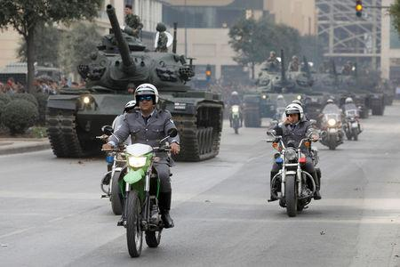 A group of policemen of motorcycles passes a convoy of tanks during the rehearsal parade for the Independence Day in Beirut