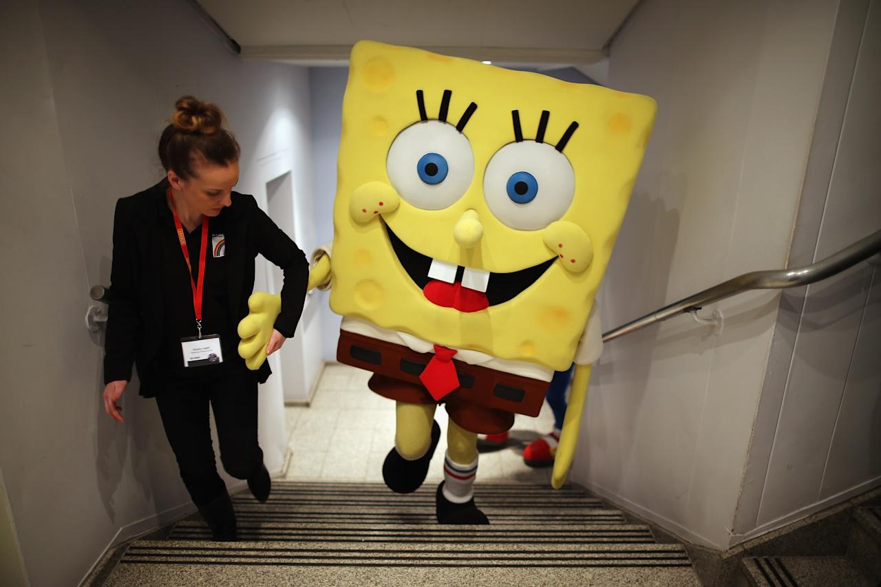 LONDON, ENGLAND - JANUARY 22:  A Sponge Bob Square Pants character is helped up a flight of stairs  during the 2013 London Toy Fair at Olympia Exhibition Centre on January 22, 2013 in London, England. The annual fair which is organised by the British Toy and Hobby Association, brings together toy manufacturers and retailers from around the world.  (Photo by Dan Kitwood/Getty Images)