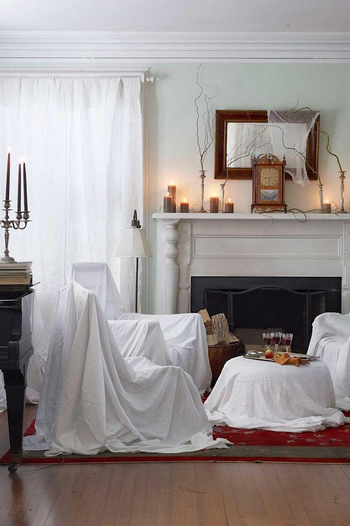 """<p>Give your living room a haunted makeover by draping your chairs and tables with white sheets. Then, string a cheesecloth """"cobweb"""" across a mirror and secure curly willow branches in candlesticks with museum wax.</p><p><a class=""""link rapid-noclick-resp"""" href=""""https://www.amazon.com/Quakehold-66111-2-Ounce-Museum-Pack/dp/B07782GN7H?tag=syn-yahoo-20&ascsubtag=%5Bartid%7C10070.g.1908%5Bsrc%7Cyahoo-us"""" rel=""""nofollow noopener"""" target=""""_blank"""" data-ylk=""""slk:SHOP MUSEUM WAX"""">SHOP MUSEUM WAX</a></p>"""