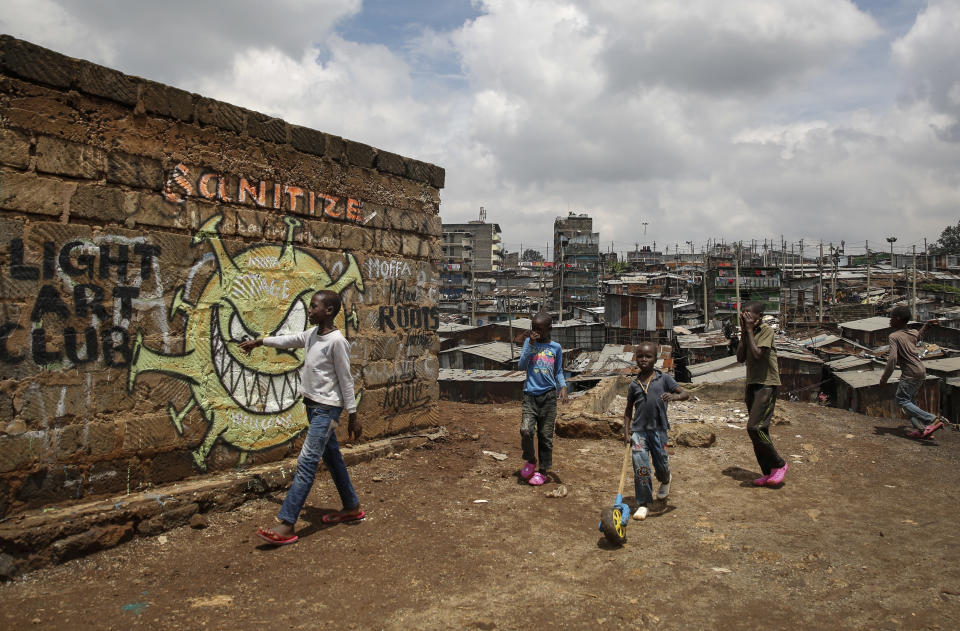 Children walk past an informational mural depicting the new coronavirus and warning people to sanitize to prevent its spread, painted by graffiti artists from the Mathare Roots youth group, in the Mathare informal settlement, of Nairobi, Kenya, Wednesday, April 22, 2020. (AP Photo/Brian Inganga)