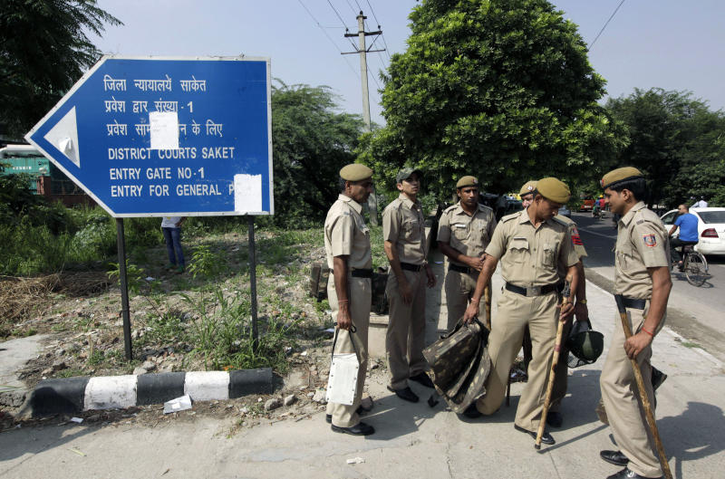 Indian policemen stand guard outside a court complex where a verdict in the Dec. 16, 2012 gang rape case is expected to be pronounced, in New Delhi, India, Tuesday, Sept. 10, 2013. The Indian court is set to deliver judgment in the fatal gang rape of a young woman on a moving New Delhi bus last year that has incensed the public and fueled debate over whether women can be safe in India. (AP Photo/Manish Swarup)