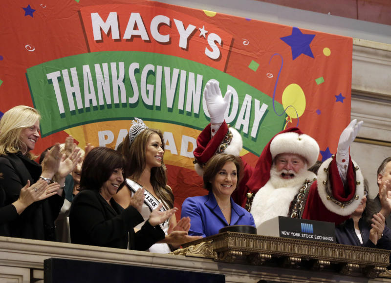 Amy Kule, second from right, executive producer of Macy's Thanksgiving Day Parade, is joined by Miss USA 2014 Nia Sanchez, and Santa Claus as she rings the New York Stock Exchange opening bell, Wednesday, Nov. 26, 2014. U.S. stocks opened little changed on Wednesday, keeping the major indexes near record levels, as investors assessed the latest reports on the economy. (AP Photo/Richard Drew)