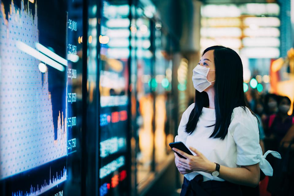 Economic and financial impact during the Covid-19 health crisis deepens. Businesswoman with protective face mask checking financial trading data on smartphone by the stock exchange market display screen board in downtown financial district showing stock market crash sell-off in red colour